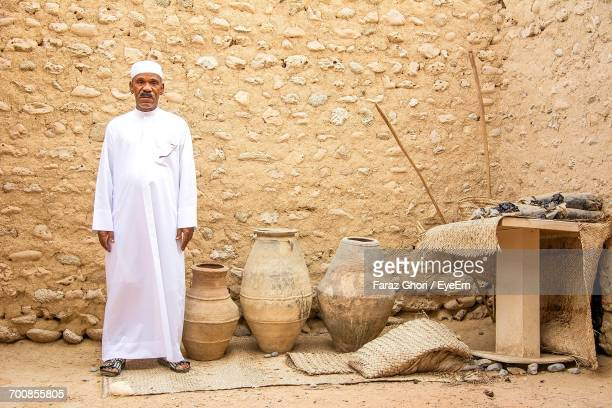 Portrait Of Man Wearing Traditional Clothing Standing Against Wall