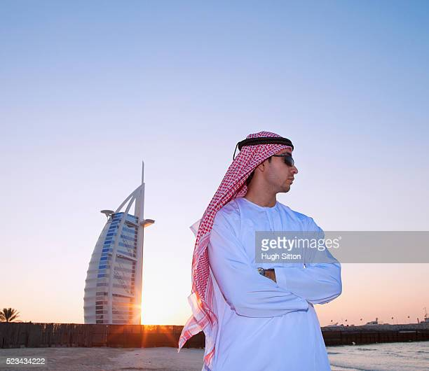 portrait of man wearing traditional clothing with burj el arab hotel in background, dubai, u.a.e - hugh sitton stock-fotos und bilder
