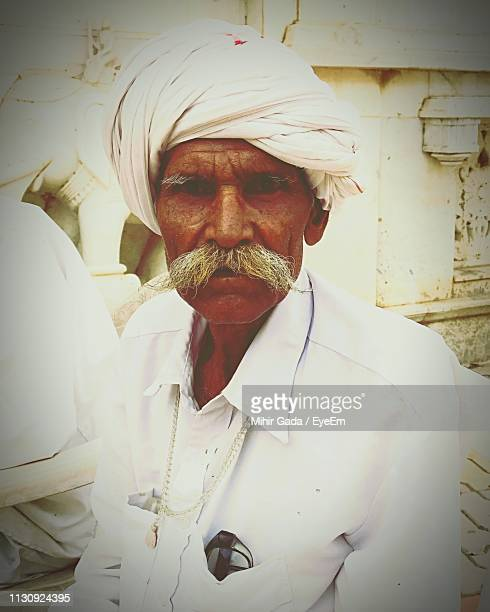portrait of man wearing turban while sitting in village - palitana stock photos and pictures