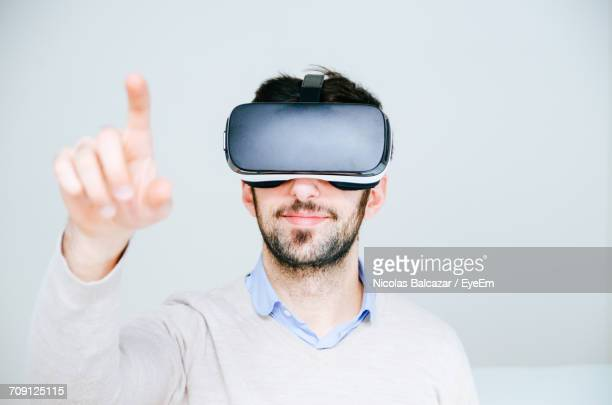 Portrait Of Man Wearing Virtual Reality Glasses Against White Background