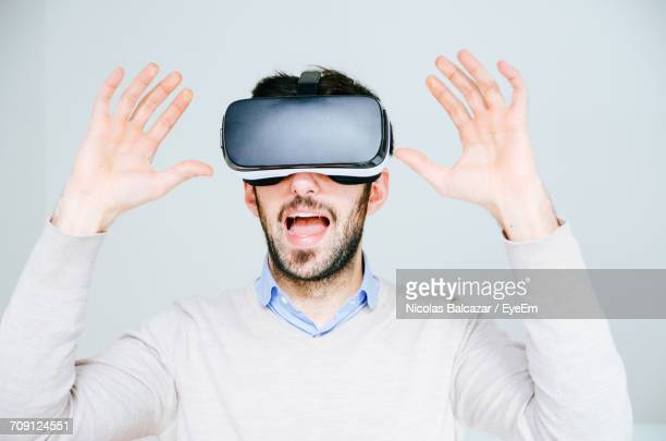 Portrait Of Man Wearing Virtual Reality Simulator Against White Background