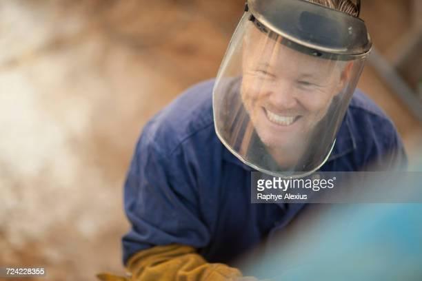 Portrait of man wearing welding mask smiling