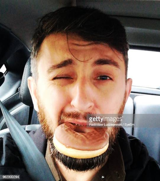 Portrait Of Man Winking While Carrying Donut In Mouth