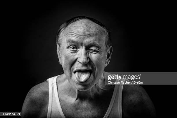portrait of man winking while sticking out tongue against black background - old man funny face black and white stock photos and pictures