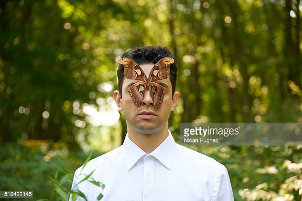 portrait of man with a butterfly over his eyes