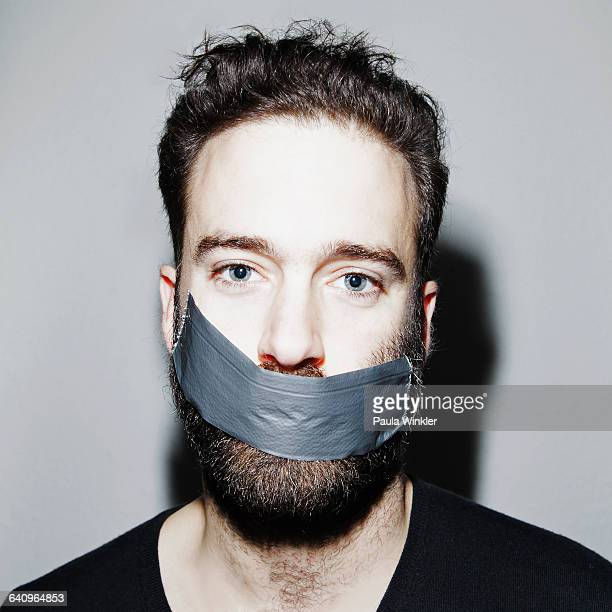 Portrait of man with adhesive tape covering his mouth