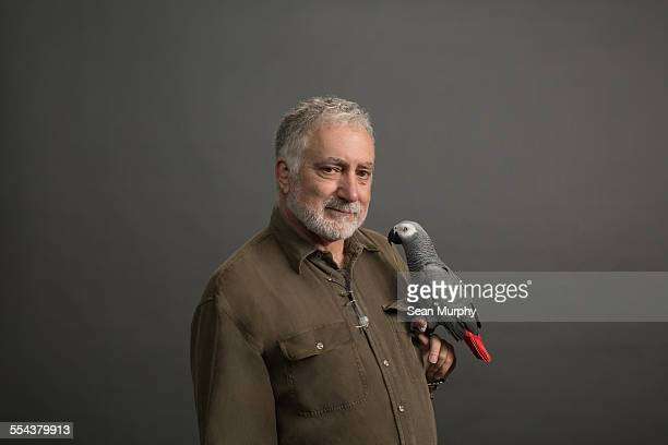 Portrait of Man with African Grey Parrot