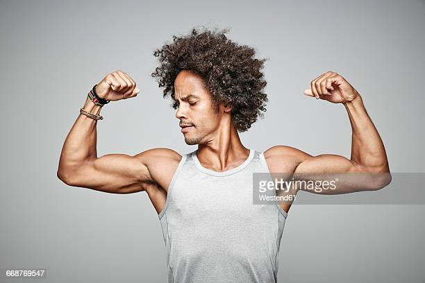 Portrait of man with afro flexing his muscles