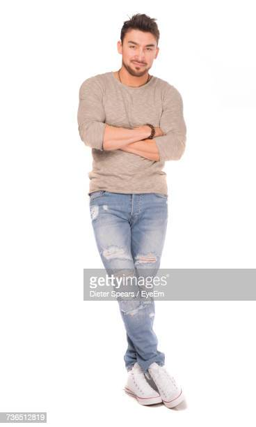 Portrait Of Man With Arms Crossed Leaning On White Background