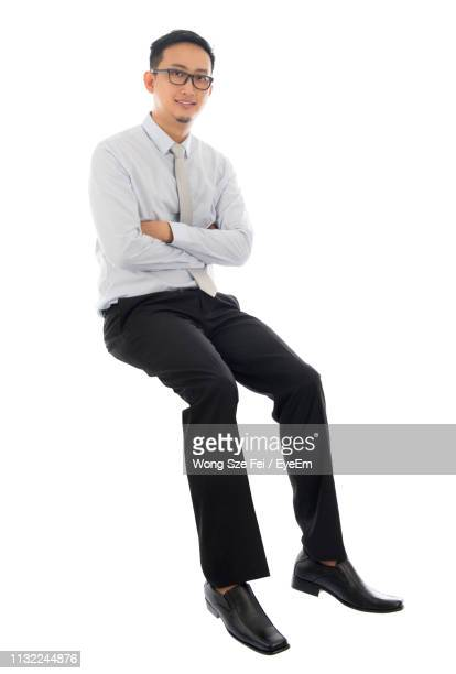 portrait of man with arms crossed sitting in mid-air against white background - sitting fotografías e imágenes de stock