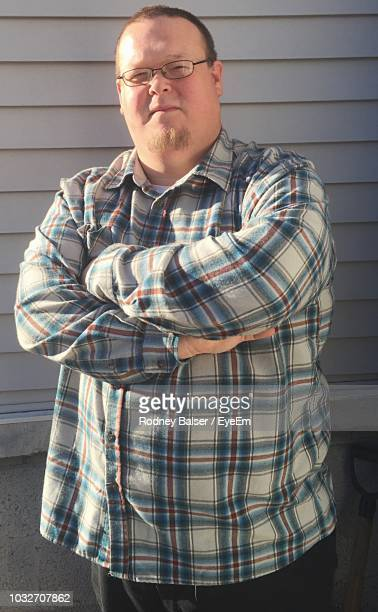 portrait of man with arms crossed standing against wall - plaid shirt stock pictures, royalty-free photos & images