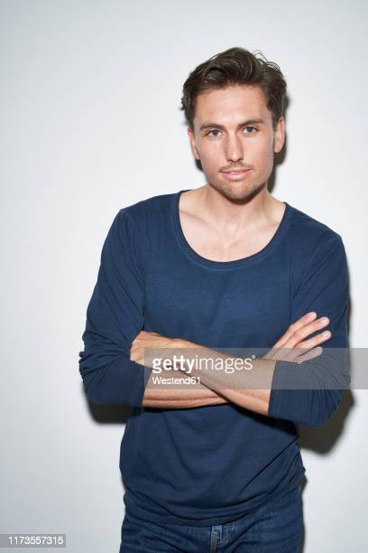 portrait of man with arms crossed wearing blue sweatshirt - langärmlig stock-fotos und bilder