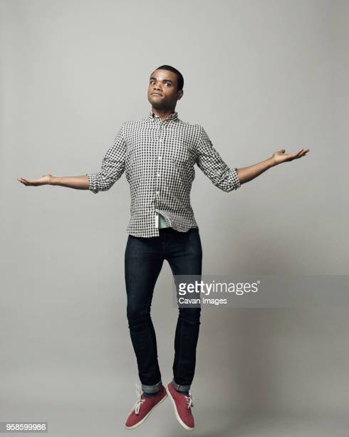 portrait of man with arms outstretched jumping against gray background - arms outstretched stock pictures, royalty-free photos & images