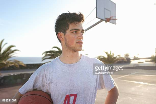 Portrait of man with ball on basketball field