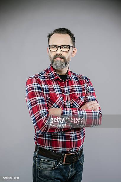 Portrait of man with beard and glasses crossing arms