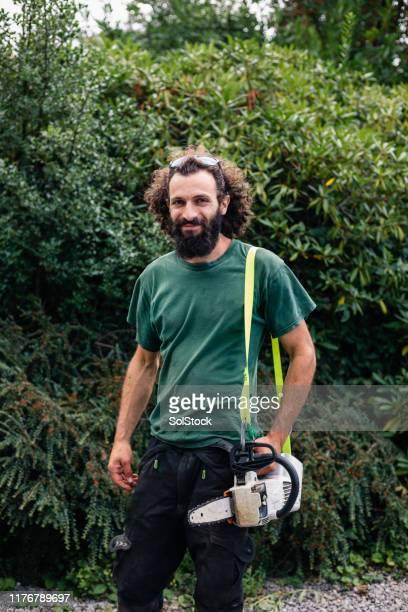 あごひげを持つチェーンソーと笑顔の男の肖像 - 造園師 ストックフォトと画像