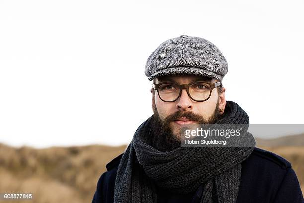 portrait of man with beard, sixpence and scarf - flat cap stock pictures, royalty-free photos & images