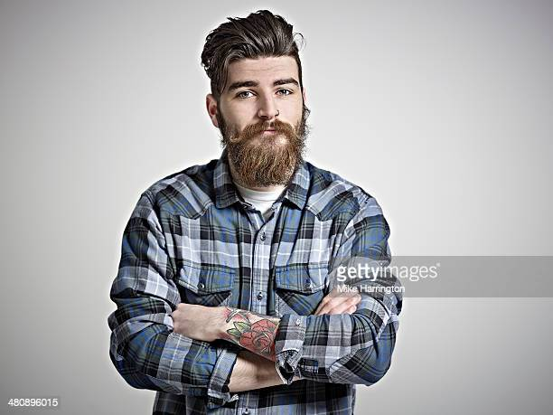 portrait of man with beard, tattoos & check shirt. - barba peluria del viso foto e immagini stock