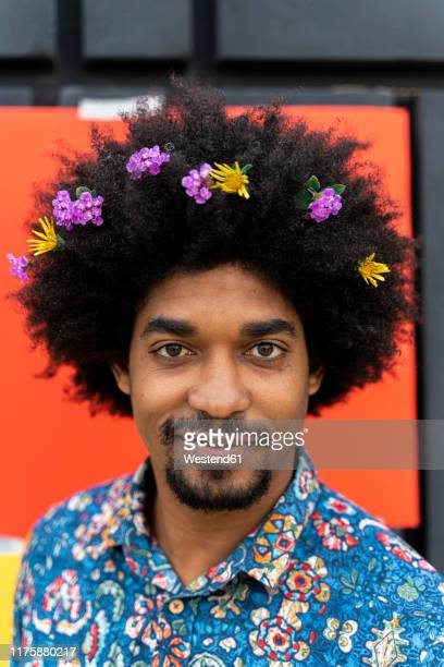 portrait of man with blossoms in his hair wearing colorful shirt - buntes hemd stock-fotos und bilder