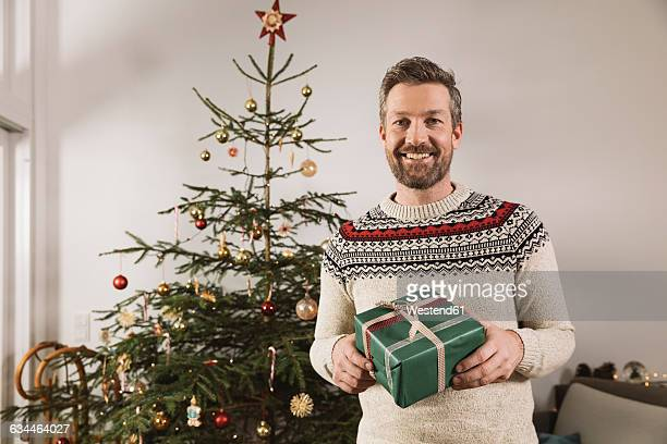 Portrait of man with Christmas gift standing in front of tree