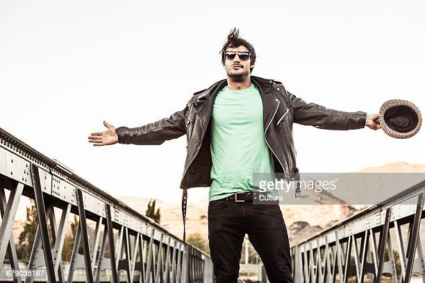 Portrait of man with cigarette in mouth wearing leather jacket and shades on rural railway bridge, Franschhoek, South Africa