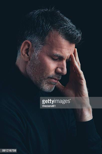 portrait of man with closed eyes and hand on his face in front of black background - endast medelålders män bildbanksfoton och bilder