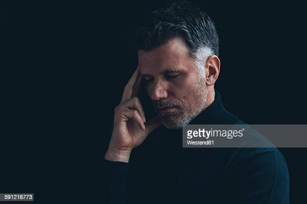 portrait of man with closed eyes and hand on his face in front of black background - coltrui stockfoto's en -beelden