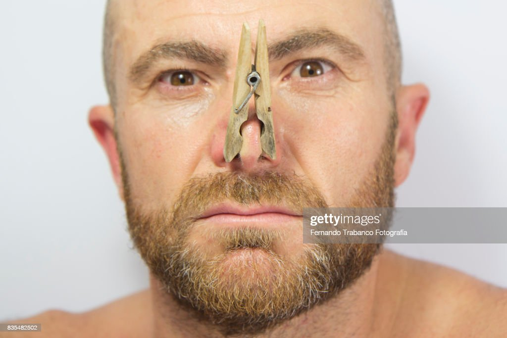 Portrait of man with clothespin on his nose : Stock Photo