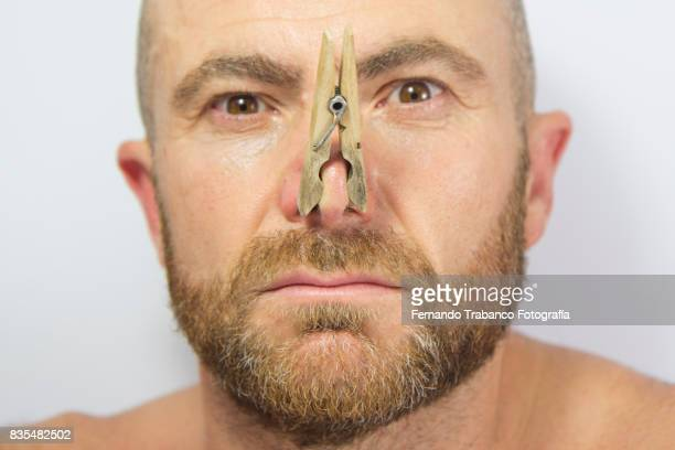 portrait of man with clothespin on his nose - defecare foto e immagini stock