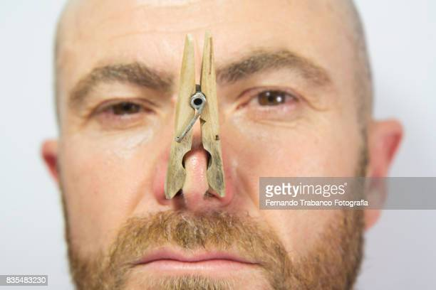 portrait of man with clothespin on his nose - clothespin stock pictures, royalty-free photos & images