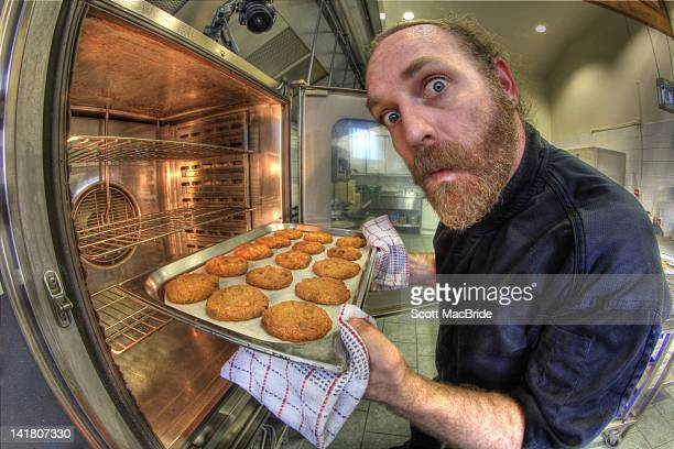 portrait of man with cookies - scott macbride stock pictures, royalty-free photos & images