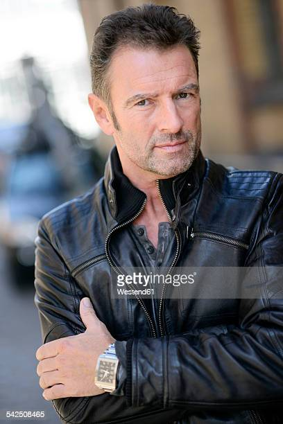 Portrait of man with crossed arms wearing black leather jacket