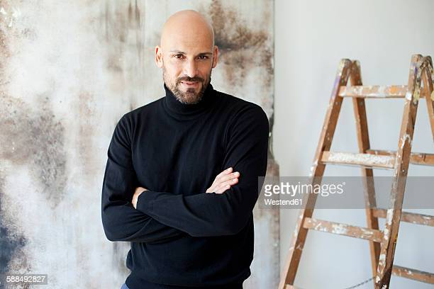 portrait of man with crossed arms wearing black turtleneck - turtleneck stock pictures, royalty-free photos & images