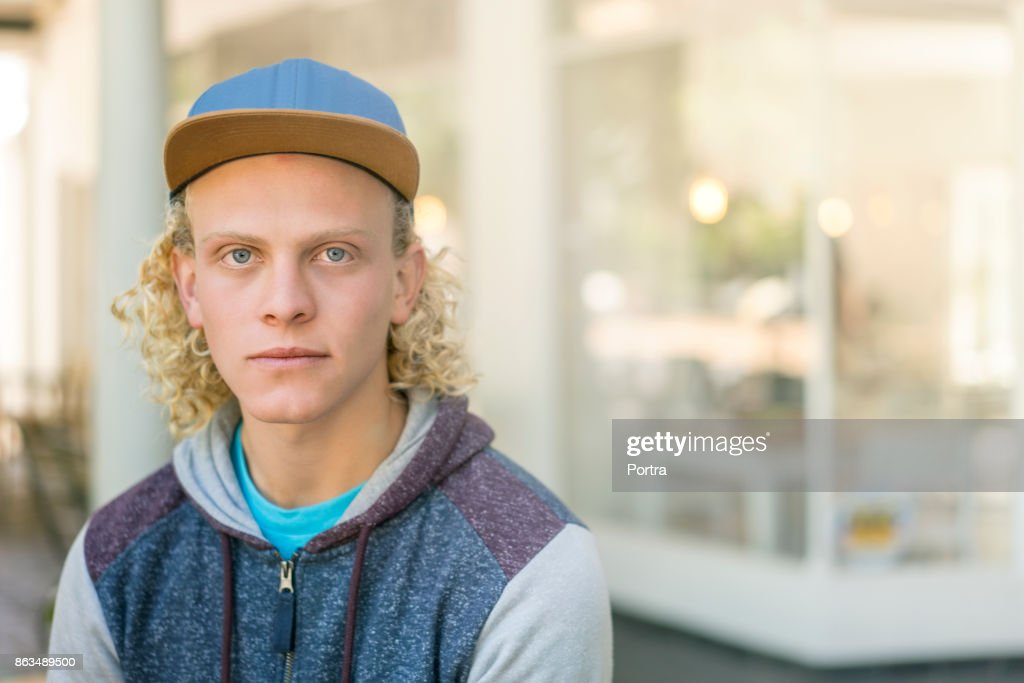 Portrait Of Man With Curly Blond Hair Wearing Baseball Cap