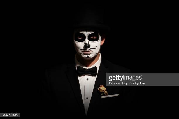 portrait of man with day of the dead make-up against black background - dia de muertos fotografías e imágenes de stock