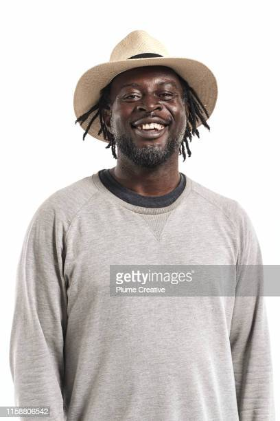 portrait of man with dreadlocks in studio - black hat stock pictures, royalty-free photos & images