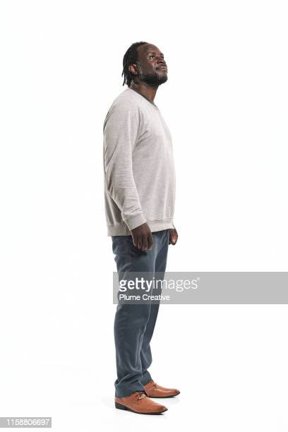 portrait of man with dreadlocks in studio - staan stockfoto's en -beelden