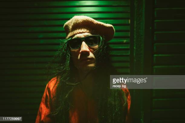 portrait of man with dreadlocks lit by neon colored lights at night - in the center stock pictures, royalty-free photos & images