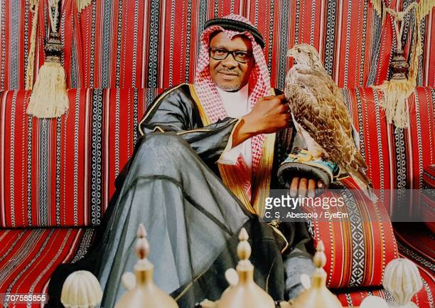 portrait of man with eagle on hand sitting on sofa - exotic pets stock pictures, royalty-free photos & images