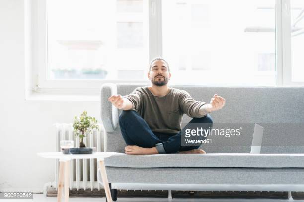 portrait of man with eyes closed sitting on the couch doing yoga exercise - einfachheit stock-fotos und bilder