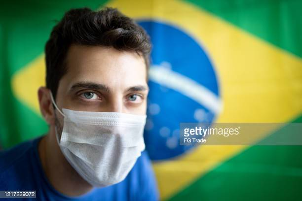 portrait of man with face mask and brazilian flag on background - brazil stock pictures, royalty-free photos & images
