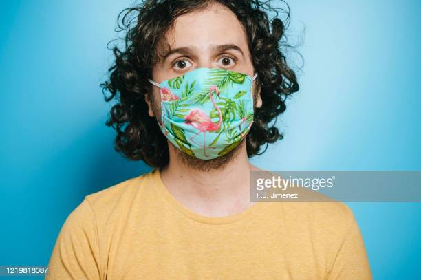 portrait of man with face mask looking at camera - masque tissus photos et images de collection