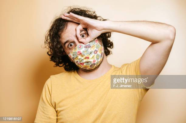 portrait of man with face mask making funny face - masque tissus photos et images de collection