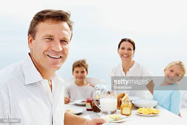 Portrait of man with family having breakfast in the background