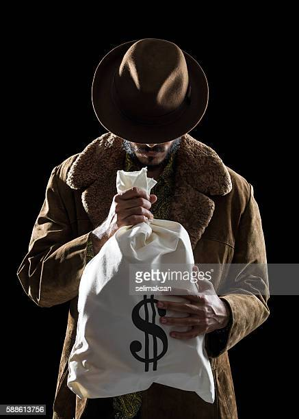 Portrait Of Man With Fedora Hat Holding Money Bag