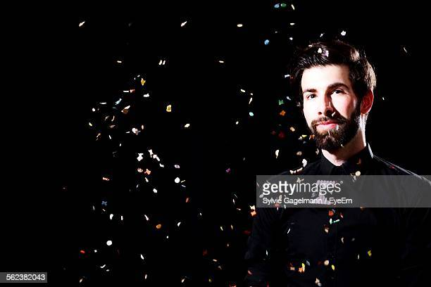 Portrait Of Man With Flying Pieces Of Paper Against Black Background