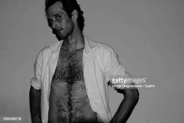 portrait of man with fully unbuttoned shirt against wall - hairy chest stock-fotos und bilder