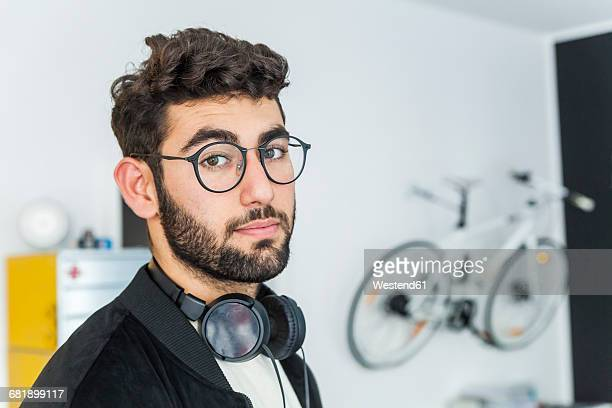 Portrait of man with glasses and headphones in a modern office