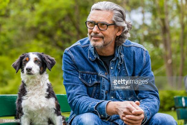 Portrait of man with grey hair and beard sitting beside his dog on a bench