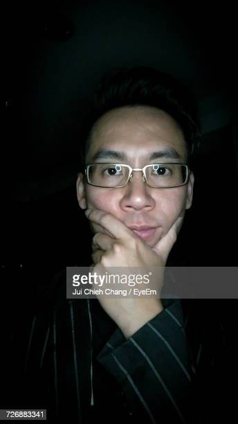 portrait of man with hand on chin in darkroom - chang jui chieh stock photos and pictures
